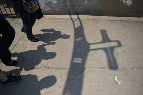 "TO GO WITH China-religion-politics-Catholic,FEATURE by Tom HANCOCK This photo taken on May 24, 2015 shows worshippers walking past the shadow of a cross at the entrance to the ""underground"" Zhongxin Bridge Catholic Church, after a service celebrating the Feast of the Ascension in Tianjin. Tianjin, 110 kilometres (68 miles) from Beijing, is thought to have up to 100,000 Catholics, and each Sunday hundreds pack the dilapidated building, some sitting on the floor or standing outside, straining to hear the bishop's sermon over the rumble of passing trucks.        AFP PHOTO / Greg BAKER"