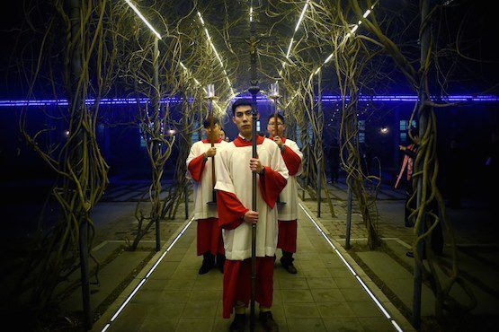 A cross-bearers prepares to enter the church as he attends the Christmas Eve mass at a Catholic church in Beijing on December 24, 2015 as Christians around the world prepare to celebrate the holy day.   / AFP PHOTO / WANG ZHAO