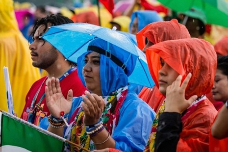 Despite the heavy rain, pilgrims from all over the world, gather to sing and dance on the Blonia Meadows in Krakow, on July 26, 2016, to celebrate the Opening Mass on the first day of the World Youth Days. Pope Francis heads to Poland Wednesday for an international Catholic youth festival with a mission to encourage openness to migrants made tougher by a fresh jihadist attack in France which has spooked and saddened pilgrims. / AFP PHOTO / WOJTEK RADWANSKI
